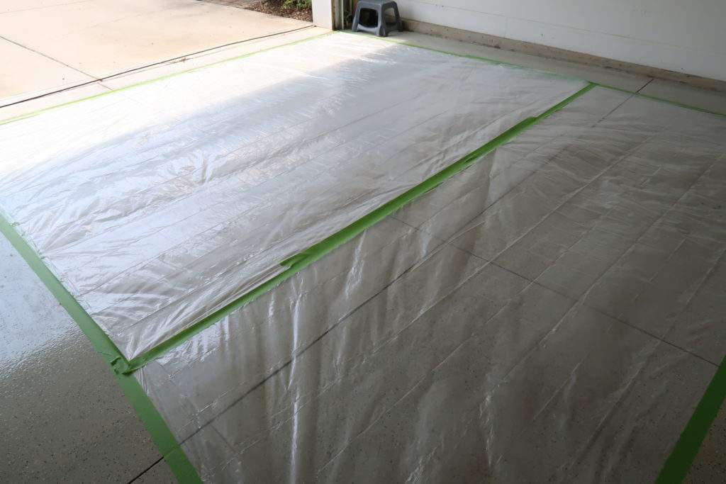 garage floor masked with plastic and taped down with frog tape