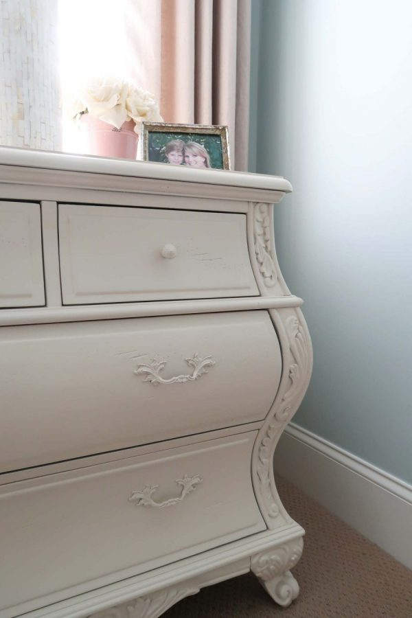 close up of carved detail on a white nightstand