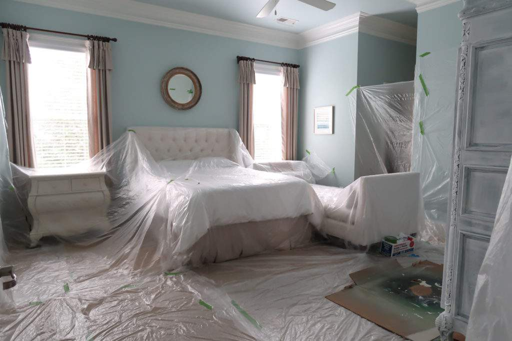 furniture in bedroom covered in plastic prior to spray painting