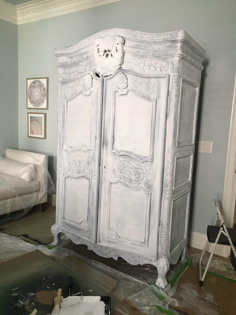 large carved french armoire against blue wall covered in white bonding primer