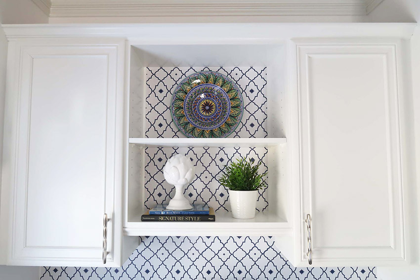 polished nickel cabinet hardware on a white cabinet with navy and white wallpaper