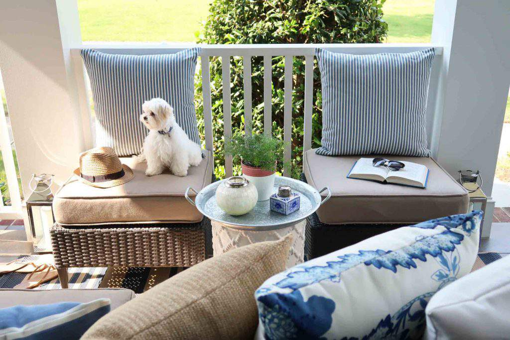 Create a sitting area using pillows up against a porch railing using blue and white pillows