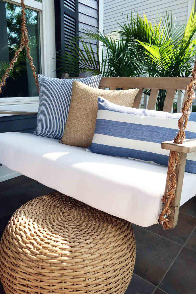 Use a wicker pouf as a foot rest under a porch swing