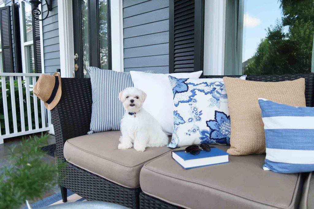 blue and white pottery barn pillows on front porch with Mick