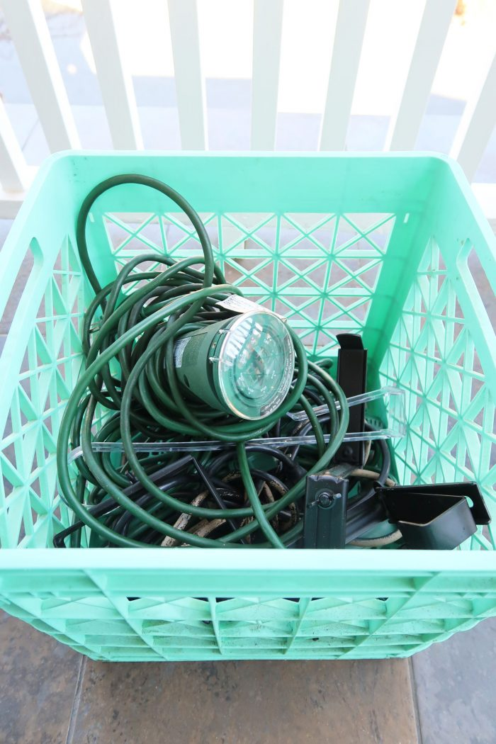 Supplies for hanging a wreath in a milk crate, timer, extension cords, and railing hangers