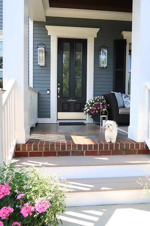 front entry way coastal blue home with new exterior lights