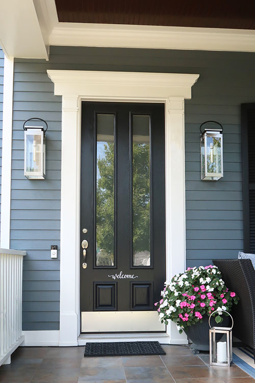 black front door on dark blue house with satin nickel coastal outdoor sconces