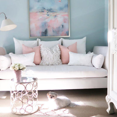 white daybed in blue room with blush pillows and white maltese