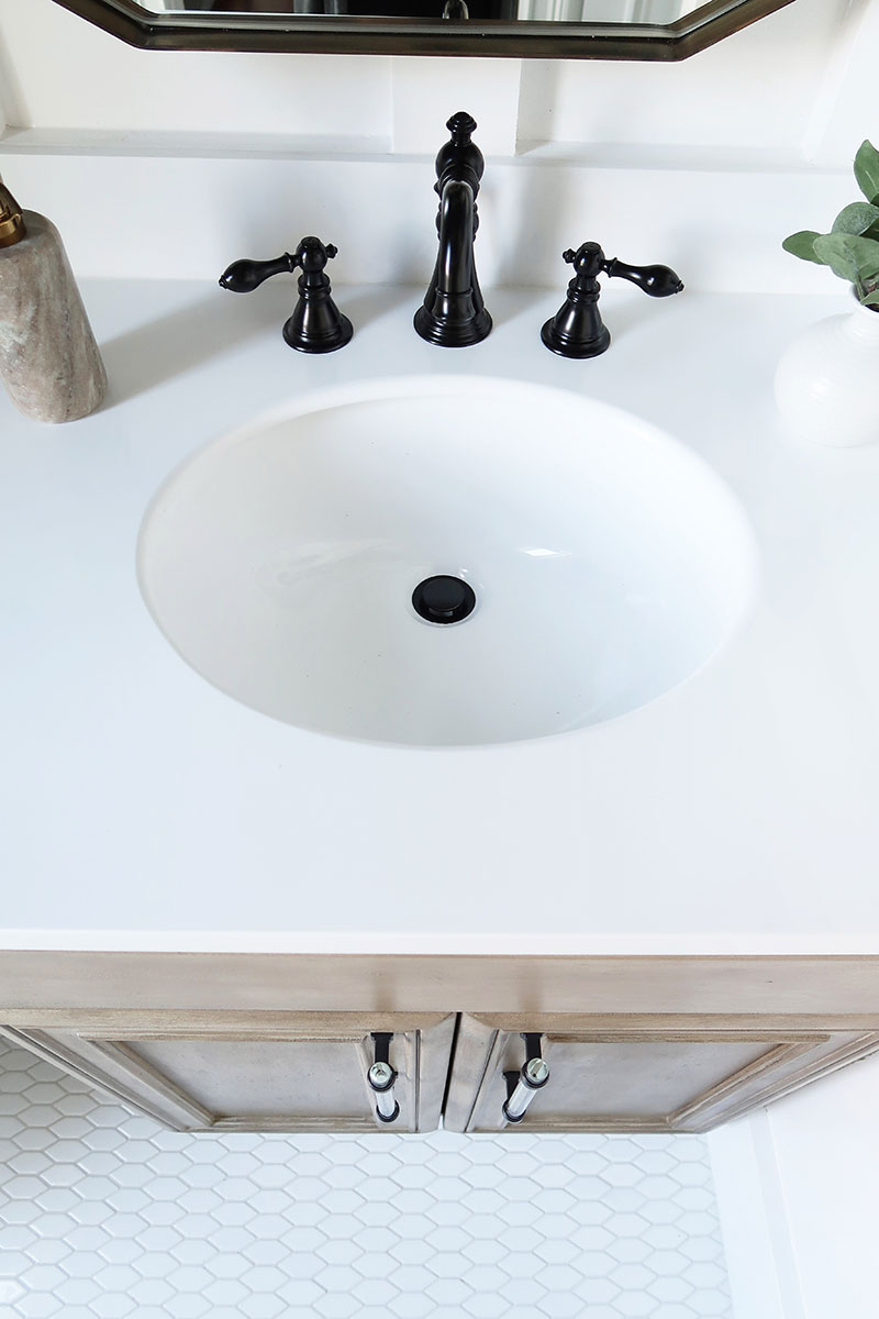 black-faucet-and-acyrlic-cabinet-hardware-showing-tile-pattern