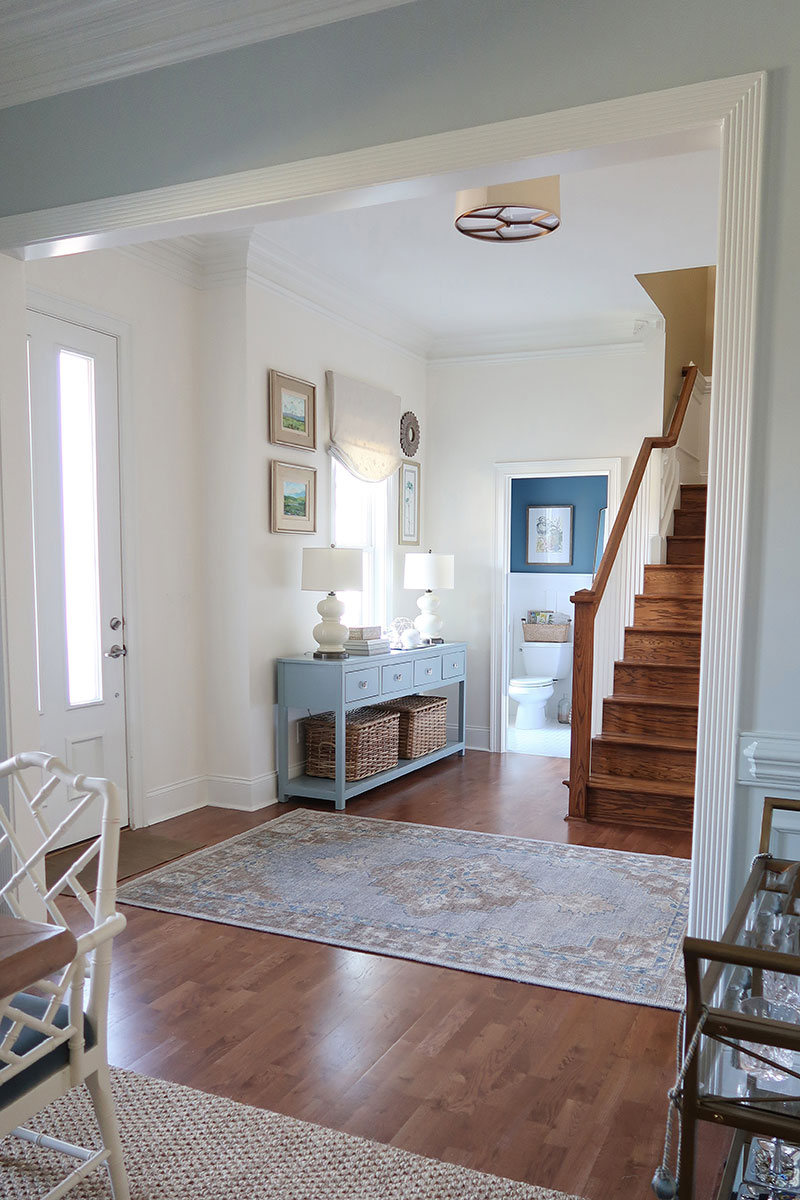 foyer-in-white-with-pottery-barn-finn-rug-blue-console-looking-into-powder-room