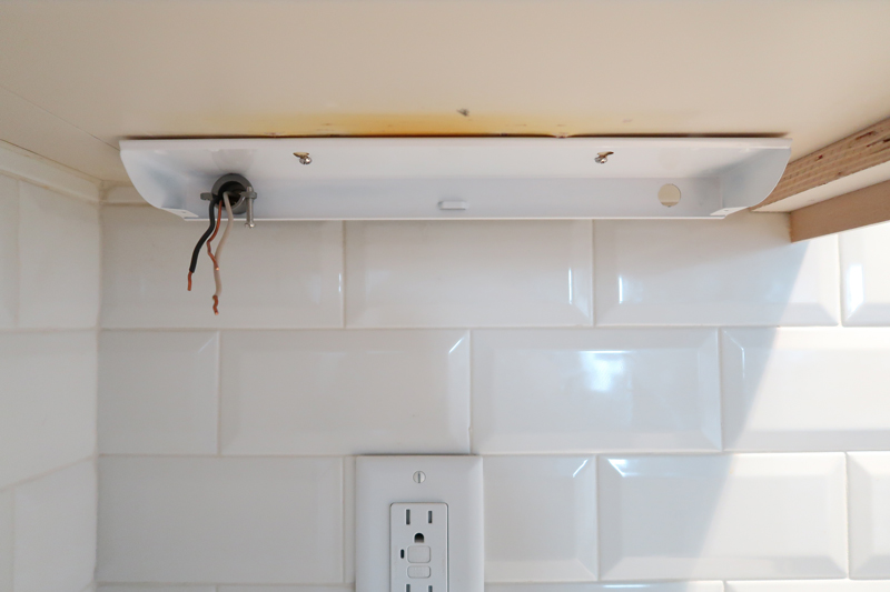 LED-light-fixture-attached-under-cabinet-with-wires-pulled-through-strain-relief