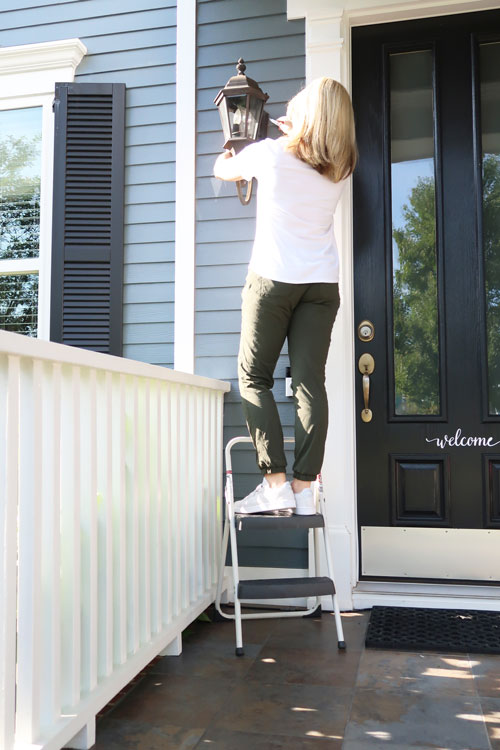 Woman-removing-exterior-sconce-outdoor-lights-from-siding