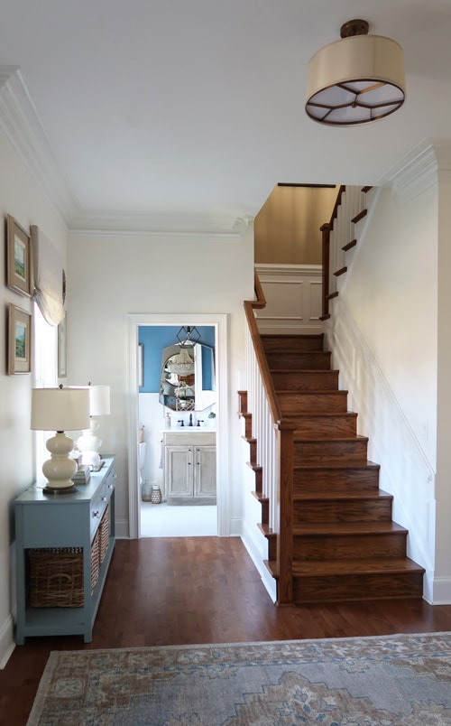 wainscotting-up-stained-stairs-white-painted-walls-blue-credenza-looking-into-powder-room