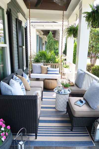 coastal-front-porch-with-striped-rug-and-pillows-blue-and-white-decor-driftwood-finish-swing-chain-wrapped-in-rope