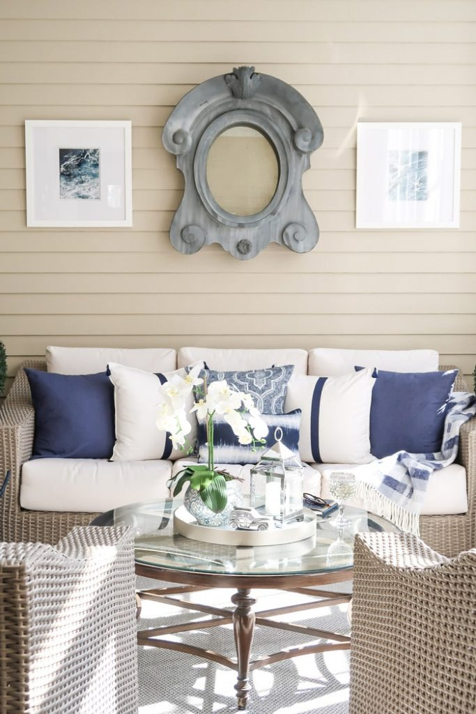 driftwood-outdoor-sofa-chairs-round-coffee-table-white-and-navy-pillows-min