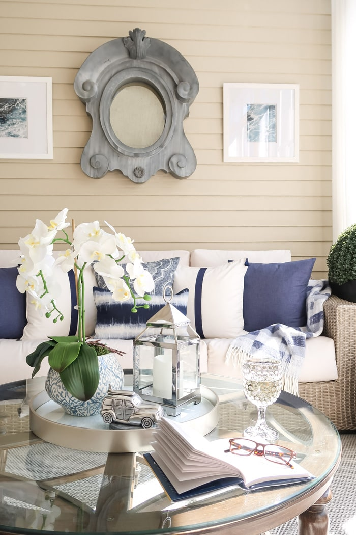 glass-of-wine-on-screened-porch-book-glass-navy-white-pillow-driftwood-sofa-min