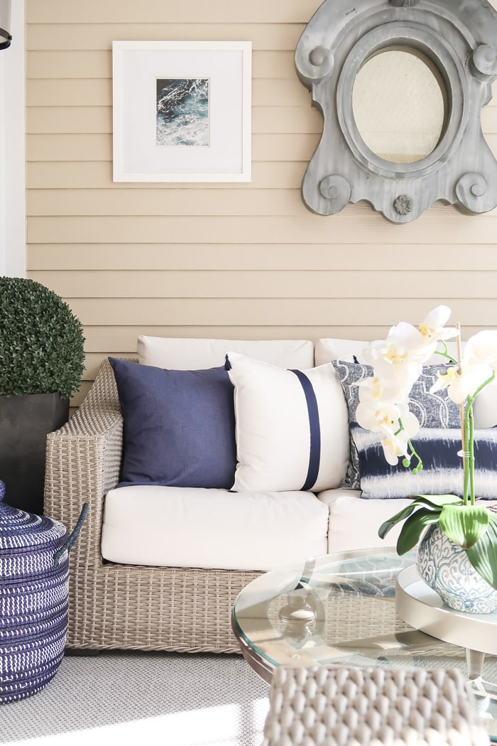 layers-of-textures-glass-round-table-orchid-blue-white-planter-round-topiary-bush-black-planter-silver-woven-rug-white-navy-pillows-min
