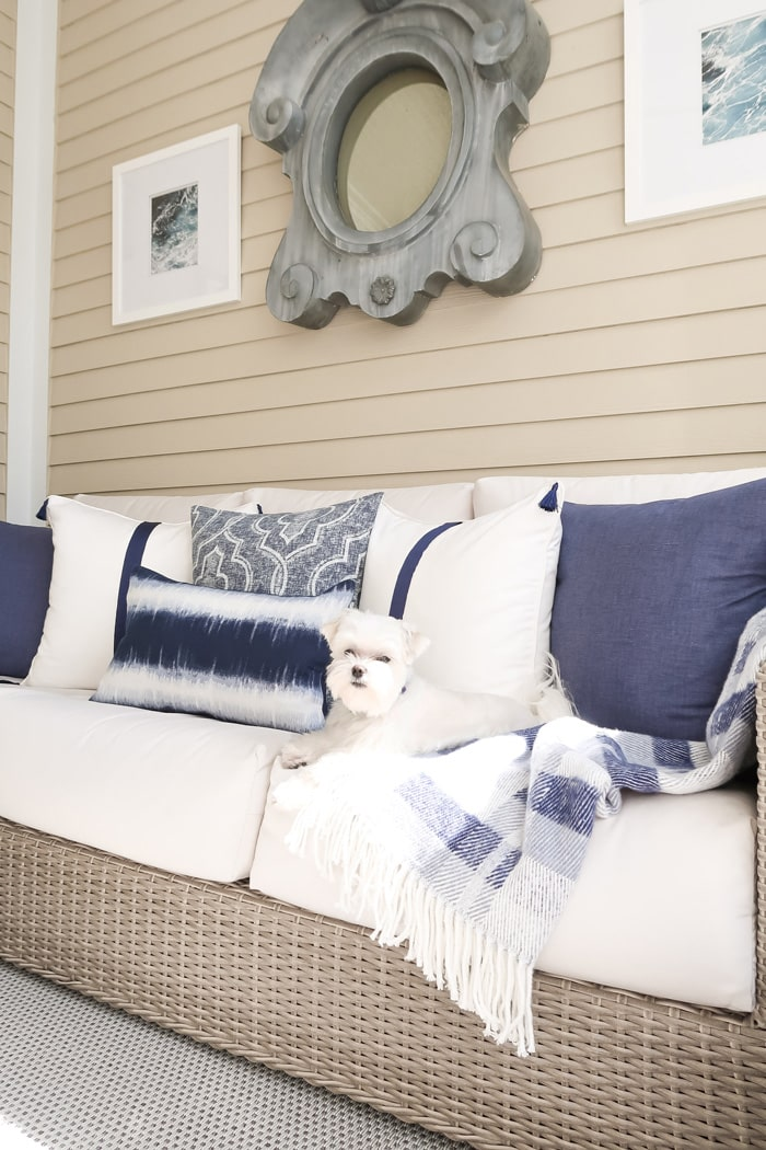 mixing-white-and-navy-pillows-on-outdoor-sofa-maltese-blue-and-white-throw-min