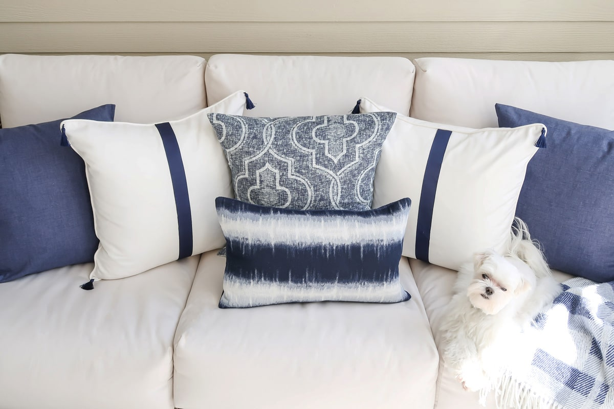 white-and-navy-pillows-outdoor-sofa-maltese-laying-in-sun-blanket-min