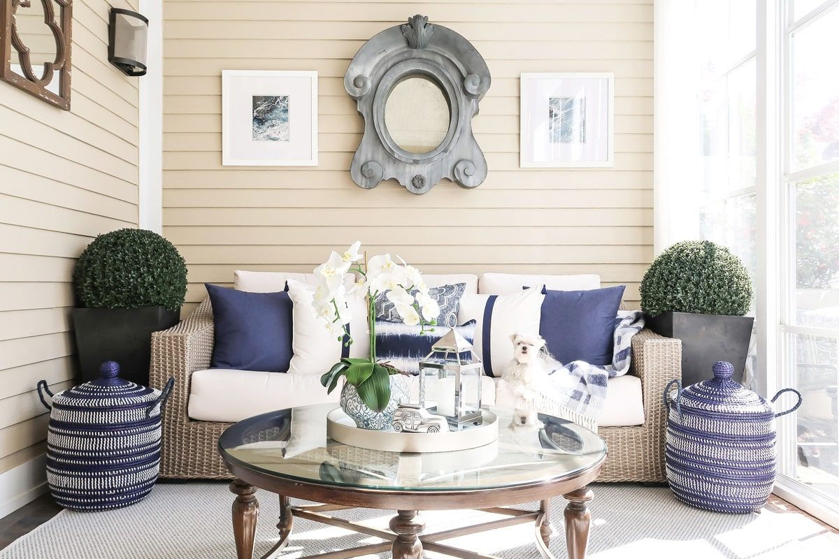 white-navy-driftwood-screened-porch-round-coffee-table-maltese-sofa-min
