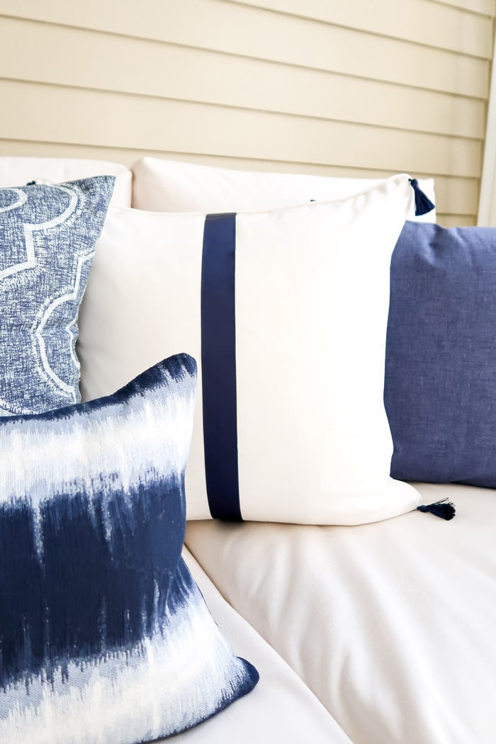 white-pillow-navy-trim-tassels-min