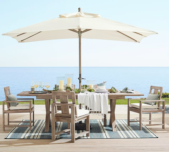 pottery barn entertaining outdoors by the ocean striped blue rug table chairs umbrella