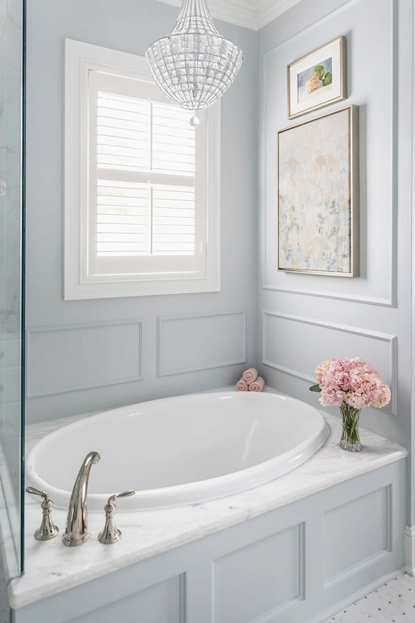 picture-frame-moulding-above-tub-nook-crystal-chandelier-pink-benjamin-moore-wales-gray-shadow-storm-marble-tub-deck-drop-in-tub-board-and-batten-tub-wall-porch-daydreamer