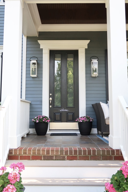 Black-front-door-with-windows-dark-blue-siding-pink-flower-entry-to-front-porch-up-stairs_3