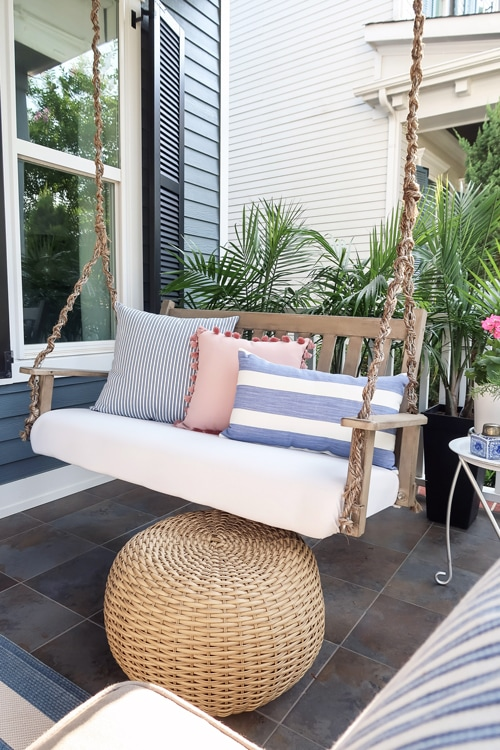 upholstered-porch-swing-seat-chaing-wrapped-in-rope-with-wicker-poof-as-foot-stool