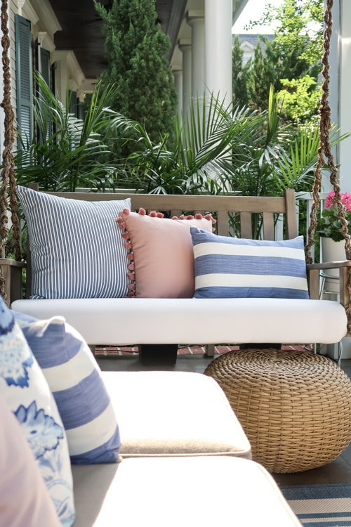 using-wicker-poof-as-foot-stool-under-upholstered-porch-swing-painted-faux-driftwood