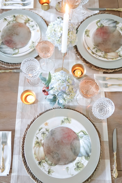 candles-reflect-light-warm-up-french-country-fall-tablescap-pumpkin-plates-gold-flatware-hobnail-glasses