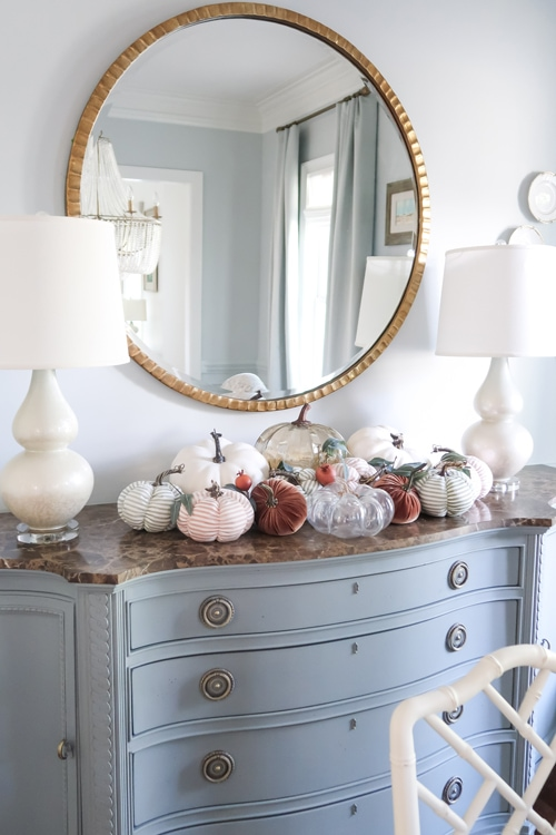 close-up-stacked-mixed-pumpkins-on-blue-dining-room-credenza