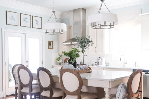 feature-white-kitchen-large-island-three-pictures-hung-in-a-row-above-doorjpg