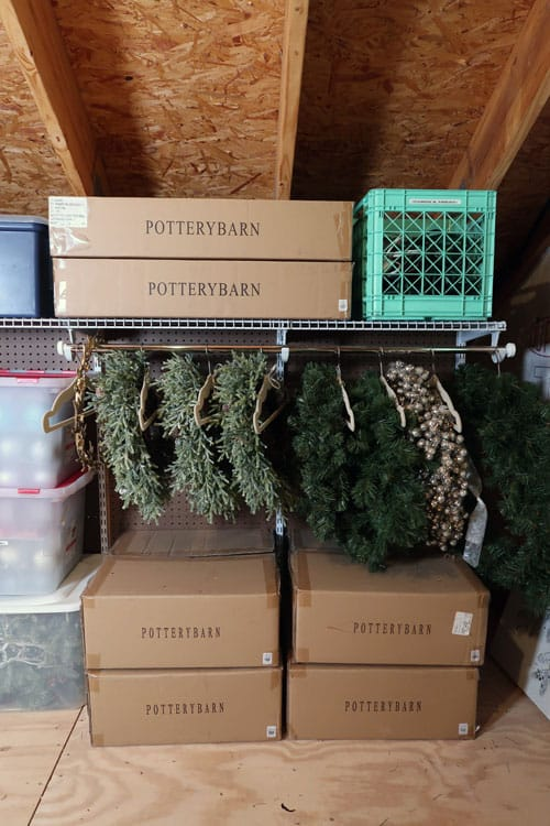 wreath-station-in-attic-orgainized-by-project-with-hangers-and-cord-wreaths-hanging-in-attic