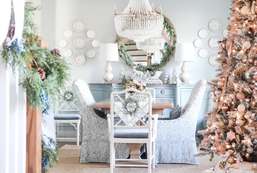 cover-view-of-dining-room-with-decorated-tree-and-garland-on-the-stairs