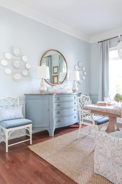blue-painted-credenza-dining-room-round-mirror-stacked-glass-pumpkins
