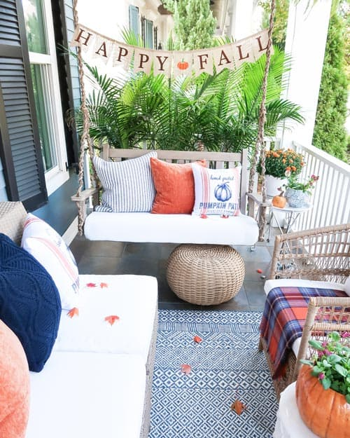 looking-down-front-porch-swing-fall-navy-orange-pillows-mums-pumpkins