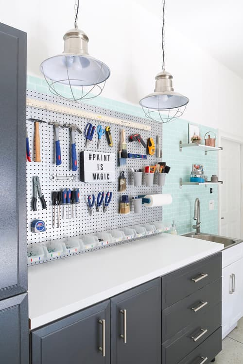 garage-pegboard-tools-pendant-lights-utility-sink-work-area-drawers-cabinet